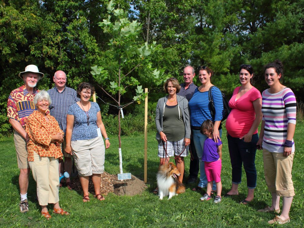 The Bustard Family and friends, along with 4-legged Ollie, stand beside their Tulip Tree which celebrates the life of Marilyn Bustard in Drimmie Park, Elora.