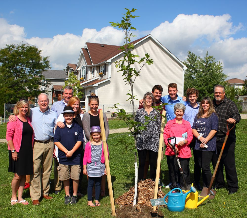 The families of John McWilliam and Ross Robertson in Pattison Park, Fergus dedicating one of two Red Oaks planted in memory John and Ross.