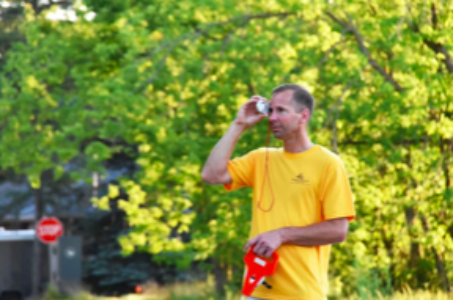 yellow shirt, neighbourwoods volunteer, surveying a tree with a measuring tape and a magnifying glass