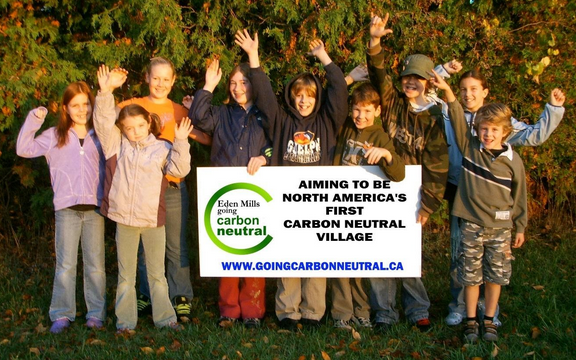 "children around sign ""aiming to be North America's first carbon neutral village"""